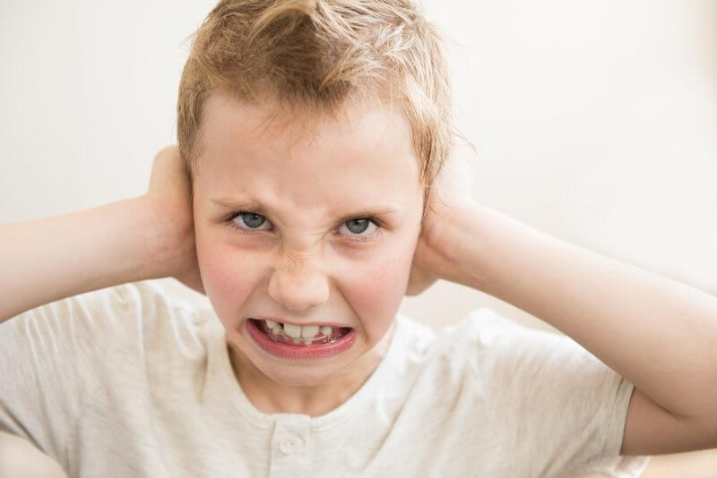 Does my child have sensory processing disorder? Boy with hands over ears.