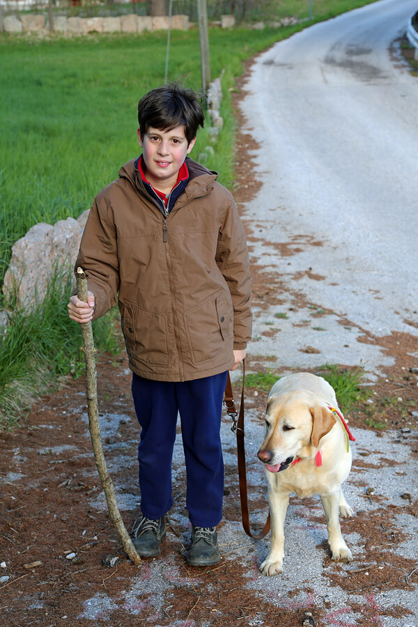 Measuring Quality of LIfe for those with ASD, starts with happiness. Boy walks a dog on a leash