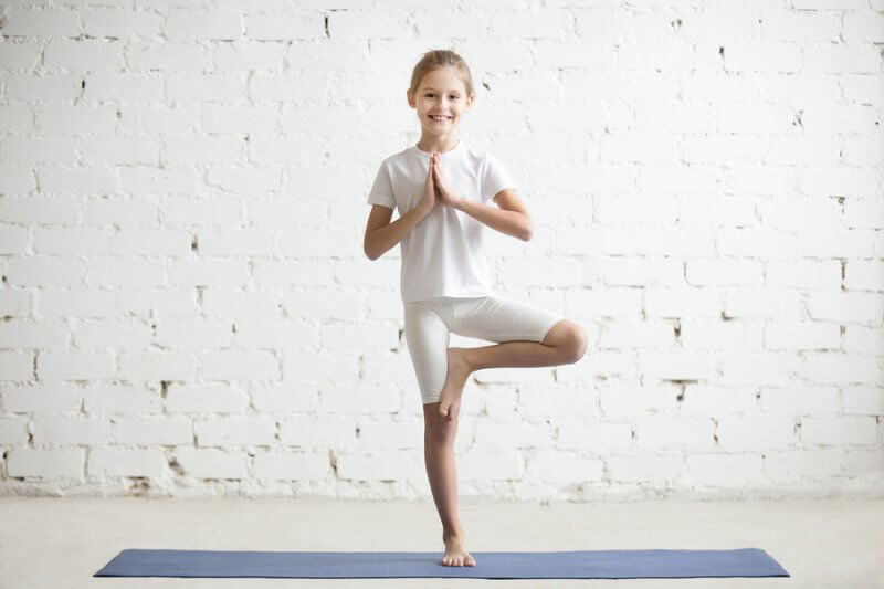 Child doing tree pose, yoga can be calming for those with autism