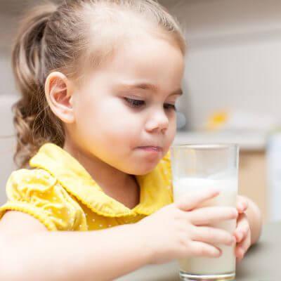 Gluten Free Dairy Free Diet for chiAutism. Child girl drinking milk at the kitchen