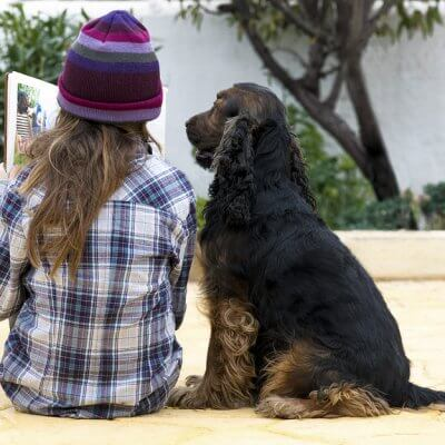 A child reading to a dog. Reading to animals can help children with autism