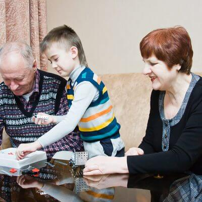 A grand mother and grand father play with their autistic grandchild