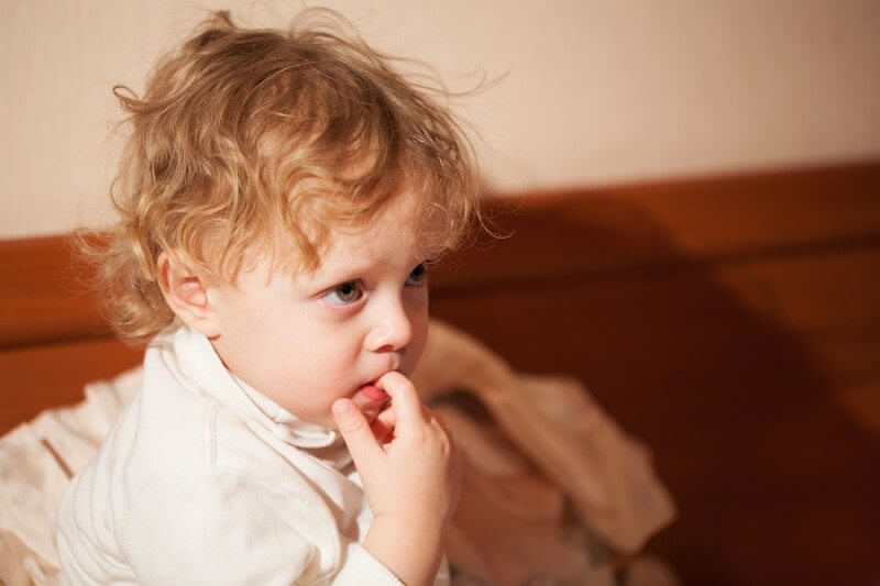 Adorable thoughtful little child with curly blond hair sitting chewing a finger and staring ahead... child with autism stimming while chewing a finger
