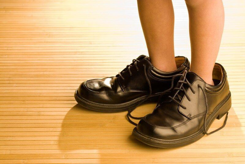 Life Skills: Big shoes to fill child's feet in large grown-up black shoes on backlit wood floor playing dress-up