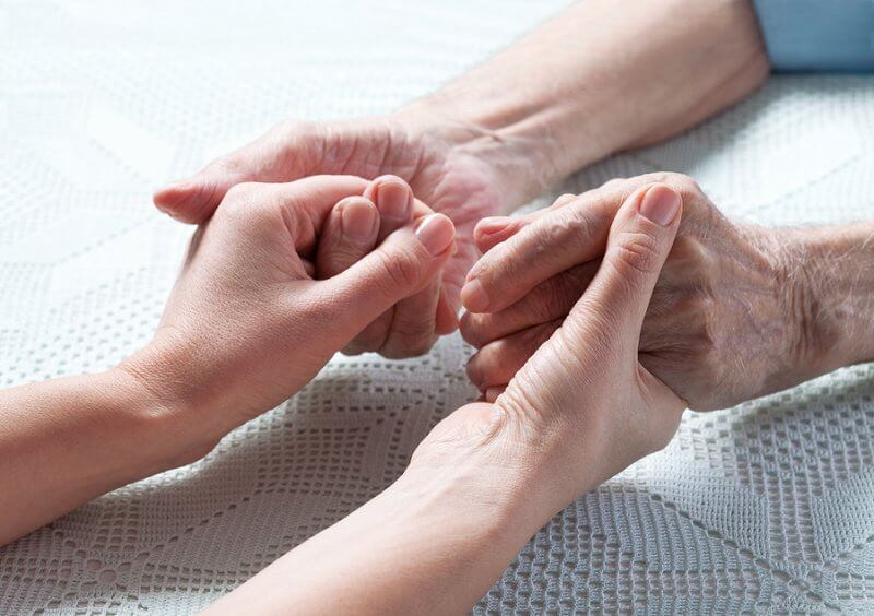 Aging caregiver holds hand of young person with disabillity