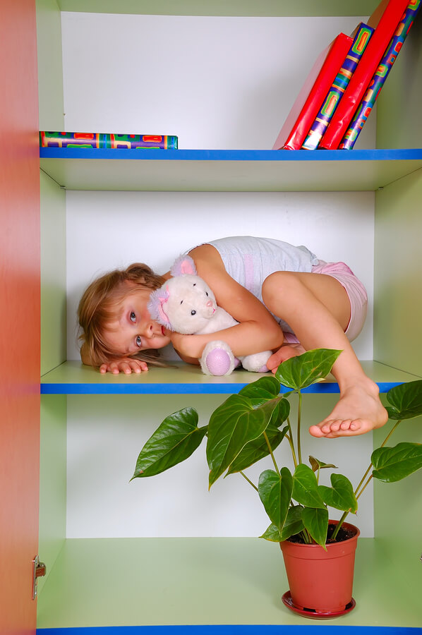 little girl with autism and unusual fears lying on a bookshelf with her toy cat