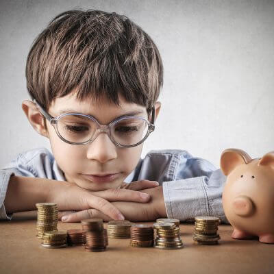 money managment for boy with autism looking at piles of money with his piggy bank