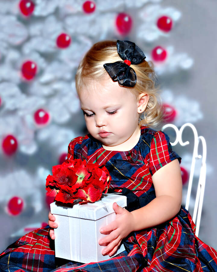 Keeping Holidays Happy and Stress Free for those with ASD, small girl in pretty dress contemplates a present warily