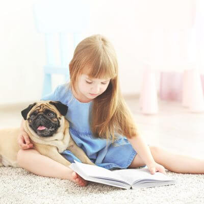 reading to dogs helps kids with autism, young girl reading to small pug