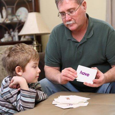 Father and son with autism studying flash cards