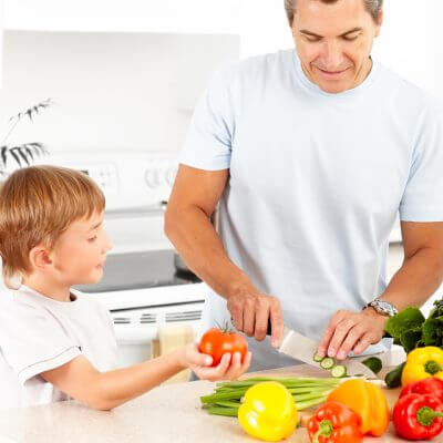 Happy family. Father and son cooking at kitchen teaching cooking to kids with autism