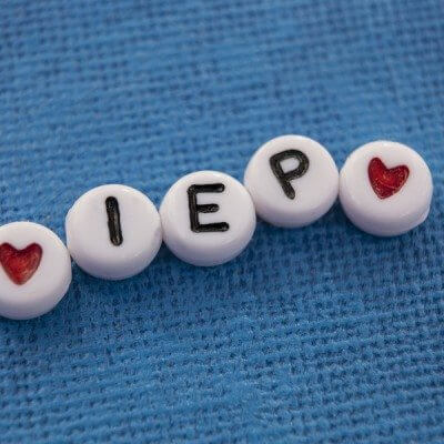Craft beads spelling out Individualized Education Plan (IEP). A plan used by public schools to support children with special needs and disabilities.