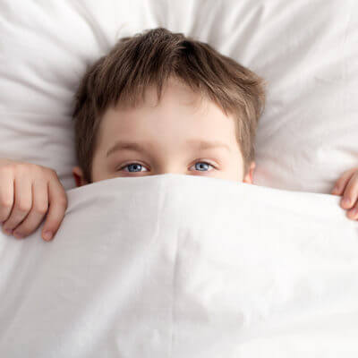 Little Boy In Bed Covering His Face With White Blanket Sleep disorders autism