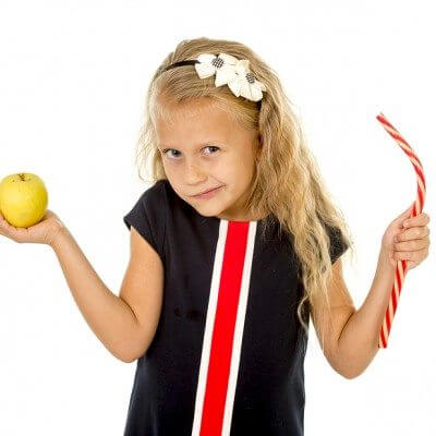 Motivation and autism: little beautiful female child with blond hair choosing dessert holding unhealthy but tasty red candy licorice and apple fruit in healthy versus unhealthy die nutrition isolated on white background