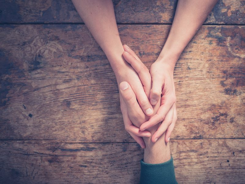 Keeping marriage strong with autism diagnosis: Close up on a man and a woman holding hands at a wooden table