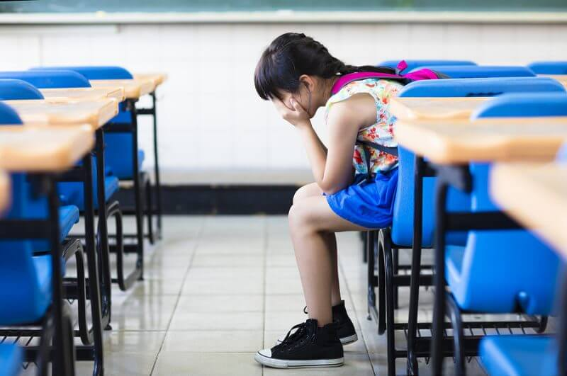 Sad Girl Sitting And Thinking In The Classroom. Girls with autism often go undiagnosed