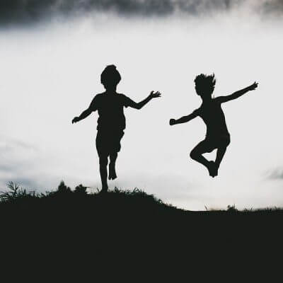 Silhouettes of siblings with autism jumping from a sand cliff at the beach.