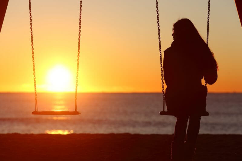 Single Woman Alone Swinging On The Beach Estate Planning for your child with disabillites