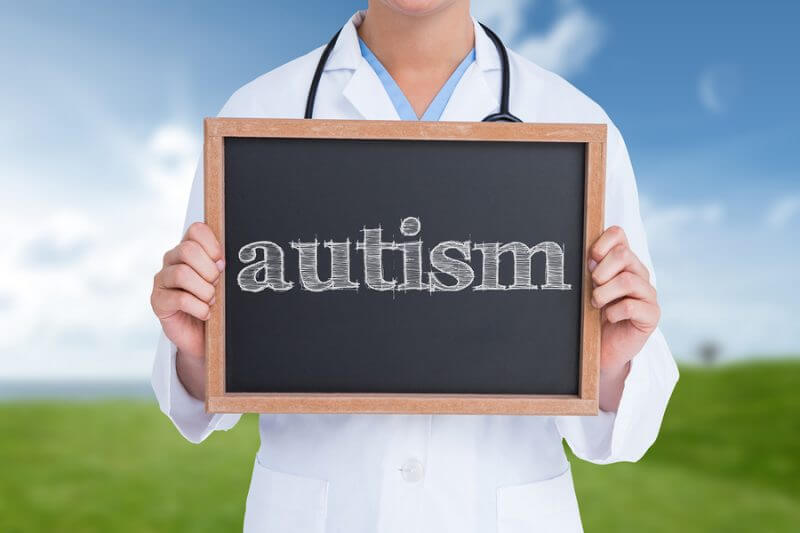The word autism and doctor showing little blackboard against field and sky. Adult autism diagnosis