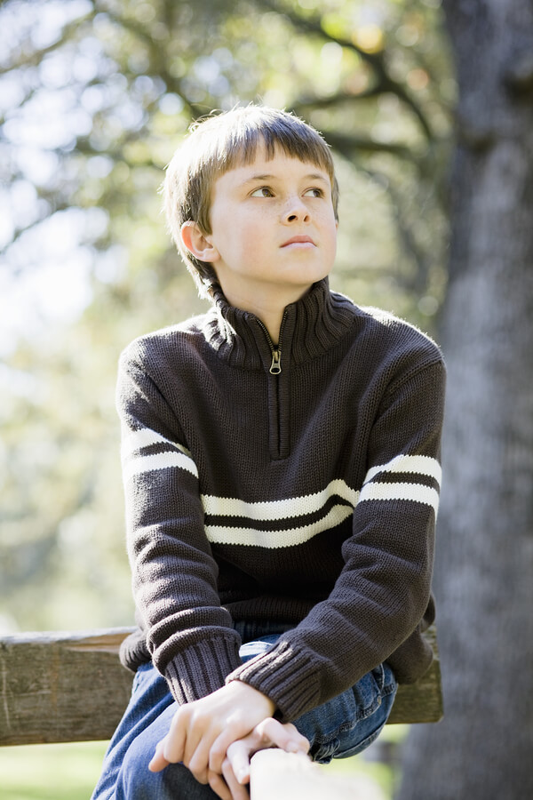 Portrait of a Cute Young Boy Sitting on a Wooden Railing Looking Away From Camera. eye contact with autism