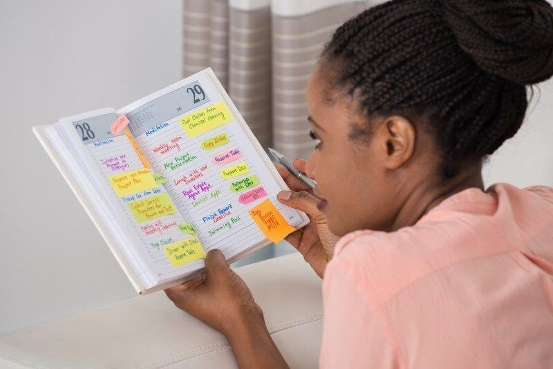 Autistic black girl looking at schedule of timetable to create predictability