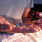 a young man in pajamas in bed about to take a blue pill