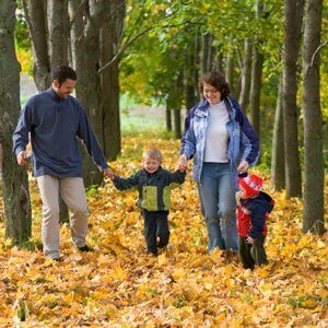 A family taking a walk through the forest in the autumn