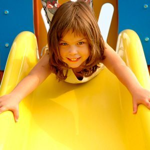 Autistic girl going down a slide