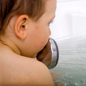 Young autistic boy playing with the shower head