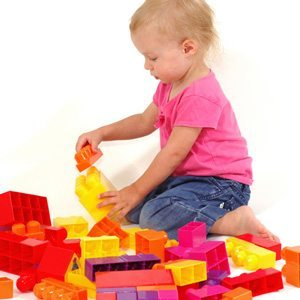 Young autistic girl playing with coloured plastic blocks