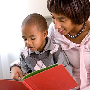 African American motehr reading with her young son