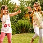 Two girls with autism in their pre teens giving a thumbs up